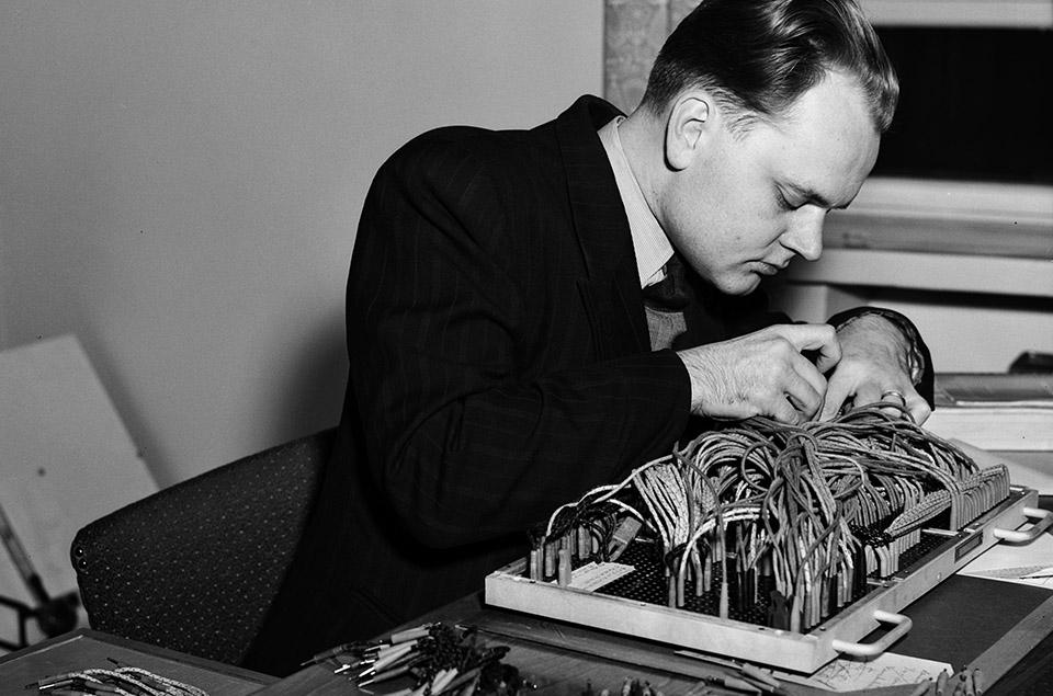Kuva: Helsingin kaupunginmuseo. Elannon reikäkorttiosaston esimies Ylermi Runko järjestää koneen kytkentöjä (1953).